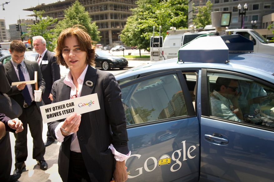 D.C. Council member Mary Cheh (Ward 3) holds up a bumper sticker she was given following her ride in Google's new self-driving Toyota Prius during a demonstration on New York Avenue NW in Washington, D.C., Thursday, May 17, 2012. (Rod Lamkey Jr./The Washington Times)