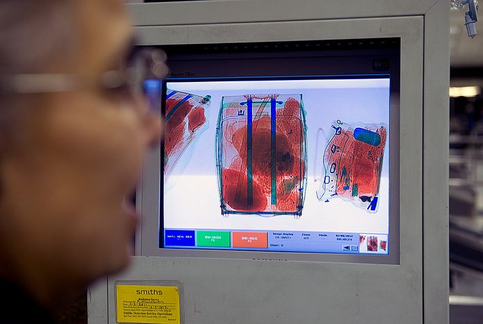 The high-tech X-ray machine used by Customs and Border Inspection agents in the Agriculture Inspection Area color-codes organic (orange), plastic (green) and metal (blue) items for easier identification. Here an officer looks at bags on the screen on Wednesday, Feb. 8, 2012 at Washington Dulles International Airport. (Barbara L. Salisbury/The Washington Times)