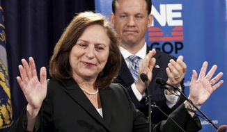 **FILE** Nebraska state Sen. Deb Fischer addresses supporters May 16, 2012, as her former opponent, state Attorney General Jon Bruning, applauds. (Associated Press)