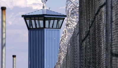 **FILE** A guard tower is seen behind the wire fence that surrounds California's Folsom State Prison, about 20 miles outside Sacramento. (Associated Press)