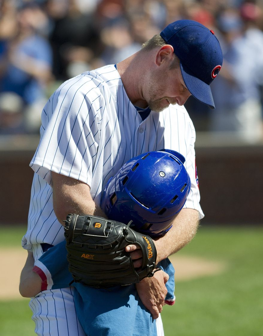 Chicago Cubs relief pitcher Kerry Wood hugs his son Justin after being taken out during the eight inning against the Chicago White Sox on Friday, May 18, 2012 in Chicago. Wood faced one batter, striking out Dayan Viciedo, in what was his final appearance before retiring from baseball. The White Sox won 3-2. (AP Photo/Brian Kersey)