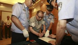 **FILE** Lai Changxing (center), once called China's most wanted fugitive, signs a warrant issued for his arrest July 23, 2011, as he arrives at the Beijing Capital International Airport in Beijing. (Associated Press/Xinhua)