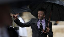 Former England football captain David Beckham waves to spectators on Thursday, May 17, 2012, in the Panathenaean stadium in Athens, during a ceremony to hand over the Olympic flame that will burn at the 2012 Summer Games in London. (AP Photo/Petros Giannakouris)