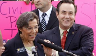 ** FILE ** In this May 8, 2012, file photo, openly gay Sen. Pat Steadman, right, D-Denver, embraces gay Sen. Lucia Guzman, D-Denver, at a rally in support of Civil Unions at the Capitol in Denver, as Senate President Brandon Shaffer is pictured in the background. (AP Photo/Ed Andrieski, File)