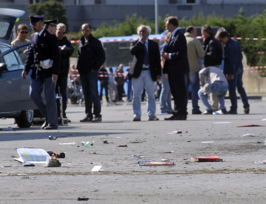 """Italian policemen, background left, walk on the site where an explosive device went off outside """"Francesca Morvillo Falcone"""" high school in Brindisi, Italy, Saturday, May 19, 2012. Several students were wounded. (AP Photo/Max Frigione)"""