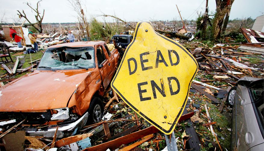 A mangled street sign stands among tornado debris in Joplin, Mo, last May. The twister killed 161 people and cost $2.8 billion in damage. Insurance is expected to cover most of the loss, but taxpayers could foot $500 million. (Associated Press)