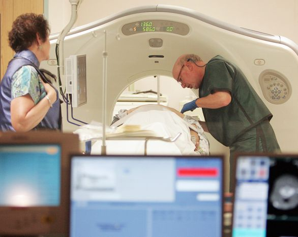 A doctor works with a patient in a CT scanner at Southern New Hampshire Medical Center in Nashua, N.H. New lung-cancer screening guidelines recommend annual scans but only for an older group of current or former heavy smokers. The guidelines were published online Sunday in the Journal of the American Medical Association. (Associated Press)