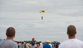 A crowd watches as a member of the Army Golden Knights lands after parachuting out of a plane at the Joint Service Open House & Air Show on Sunday at Andrews Air Force Base in Maryland. This year marked the 55th anniversary of the show that includes both vintage and present-day aircraft. (Barbara L. Salisbury/The Washington Times)
