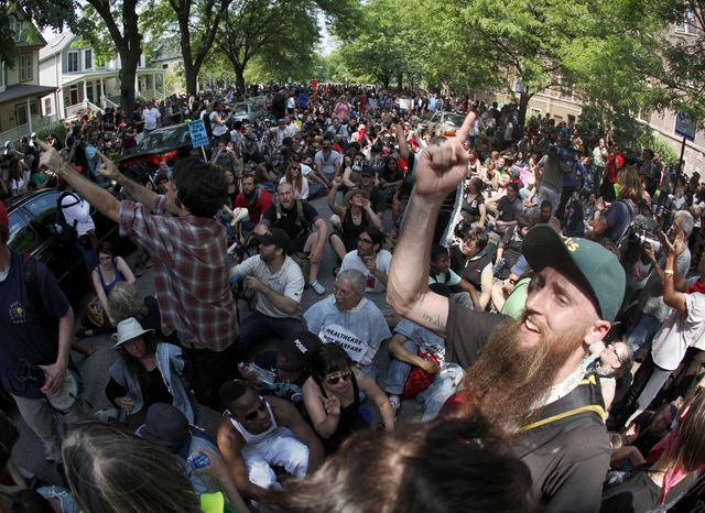 Occupy Chicago protesters sit in the street outside Chicago Mayor Rahm Emanuel's house during a march and demonstration on Saturday, May 19m 2012, in Chicago. (AP Photo/Charles Rex Arbogast)