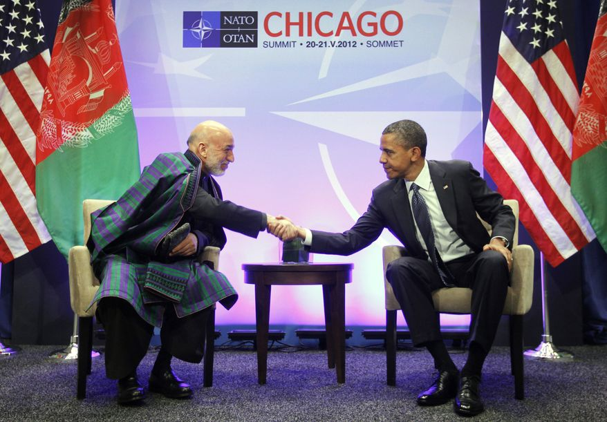 President Obama (right) shakes hands with Afghan President Hamid Karzai during their meeting at the NATO summit in Chicago on Sunday, May 20, 2012. (AP Photo/Pablo Martinez Monsivais)