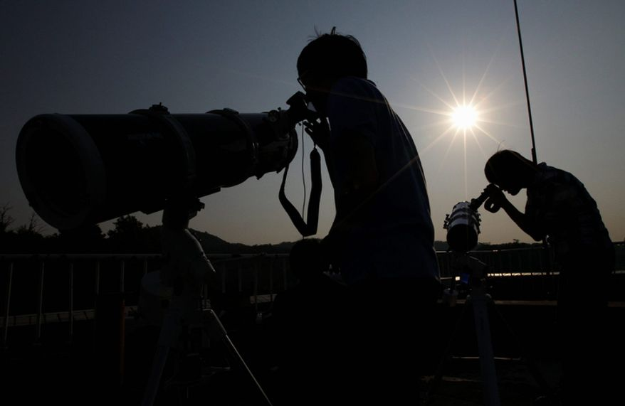 South Korean astronomy students use telescopes to observe an annular solar eclipse in Seoul, South Korea, Monday, May 21, 2012.  (AP Photo/Lee Jin-man)