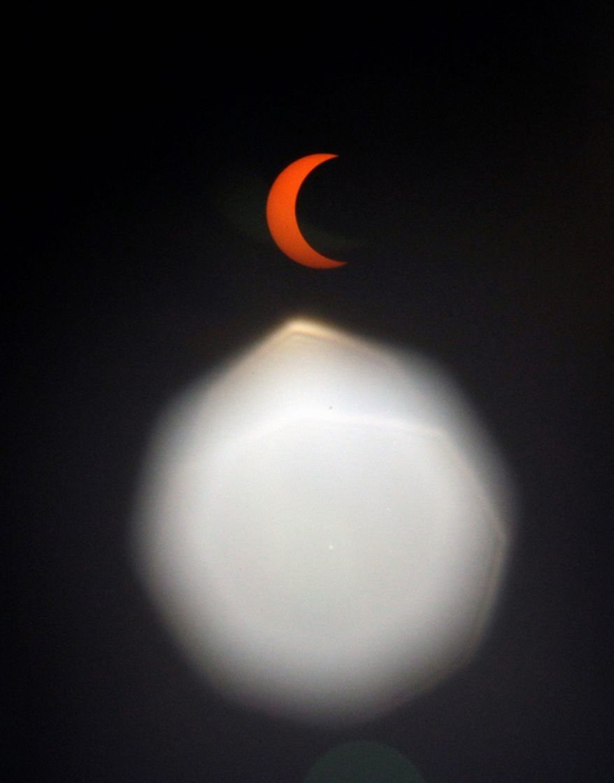 """An annular solar eclipse is seen through special sunglasses in Seoul, South Korea. Millions of Asians watched as a rare """"ring of fire"""" eclipse crossed their skies early Monday. The annular eclipse, in which the moon passes in front of the sun leaving only a golden ring around its edges, was visible to wide areas across the continent. (AP Photo/Lee Jin-man)"""