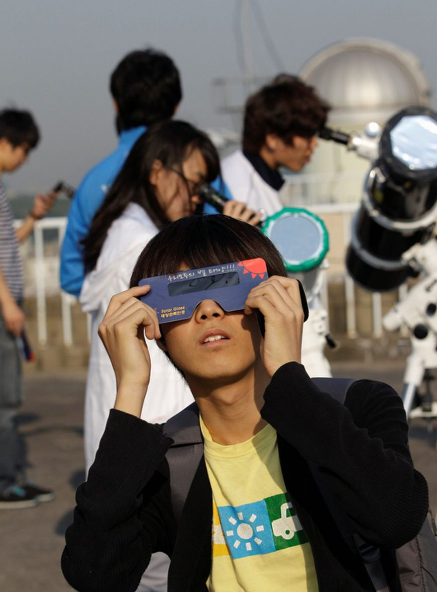 South Korean astronomy students use telescopes and special sunglasses to observe an annular solar eclipse in Seoul, South Korea. (AP Photo/Lee Jin-man)