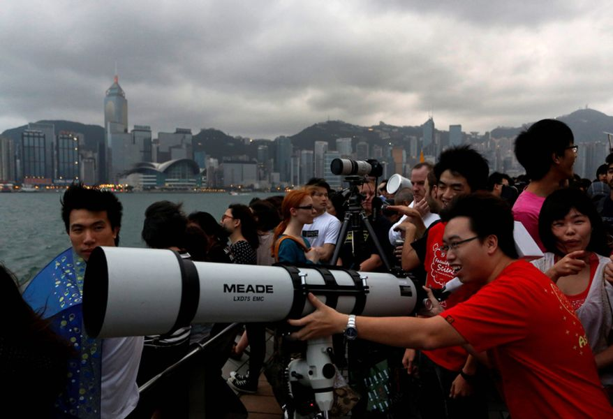 Hong Kong stargazers use a telescope to observe an annular solar eclipse along the Victoria Habour in Hong Kong.  (AP Photo/Vincent Yu)