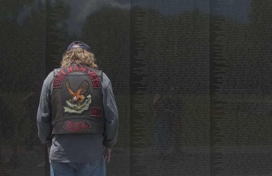 """At the Vietnam Veterans Memorial wall in NW Washington, Michael """"Trumpet"""" Willis pays homage to colleagues who died during the Vietnam war as the 18th annual Rolling Thunder ride takes place, Sunday, May 29, 2005.  Willis served in Vietnam in 1971. ( Allison Shelley / The Washington Times )"""