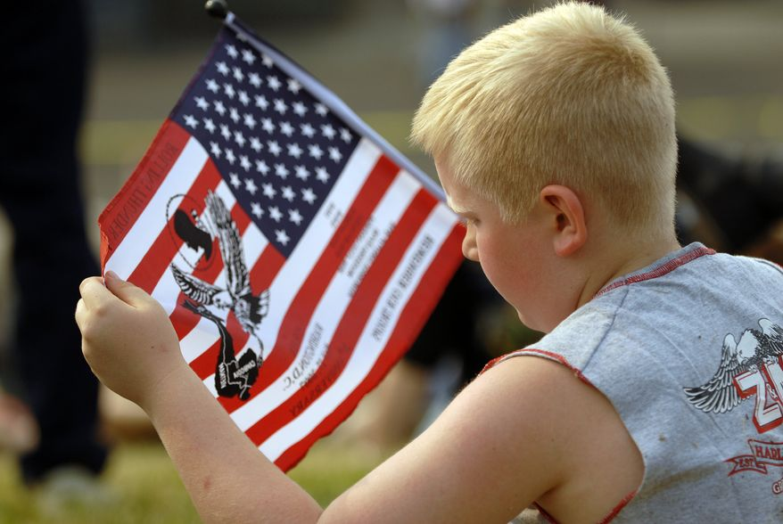 Eight-year-old Mitchell Tonkin, from Pennsylvania, takes a closer look at his flag while waiting to join this year's 'Rolling Thunder' at one of the Pentagon's parking lots near Pentagon City, Va, Sunday, May 27, 2007. Tens of thousands of motor cyclists, of whom many served in the U.S. Military, gathered first on the parking lots around the Pentagon as early as 7am this morning before crossing over to the District on Memorial Bridge then heading towards the U.S. Capitol on Constitution Avenue and finally returning back to the Lincoln Memorial on Independence Avenue. The event draws a huge crowd of visitors to the National Mall and many could hear the 'Rolling Thunder' for several hours. (Astrid Riecken/The Washington Times )