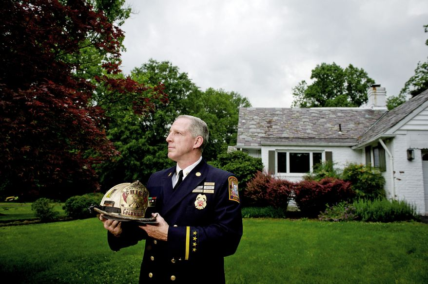 Battalion Fire Chief Kevin B. Sloan stands in front of his parents' home in Kensington. He said the shift change that followed his transfer is making it difficult for him to help care for his elderly parents. He plans to file a complaint challenging the transfer ordered by Fire Chief Kenneth Ellerbe. (Rod Lamkey Jr./The Washington Times)