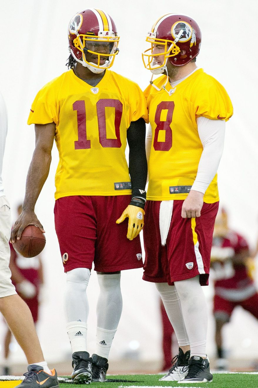 Redskins rookie quarterback Robert Griffin III (10) and Rex Grossman, the starter for most of the 2011 season, share a moment during the first organized team activity. Griffin was the Heisman Trophy winner last year at Baylor. (Andrew Harnik/The Washington Times)
