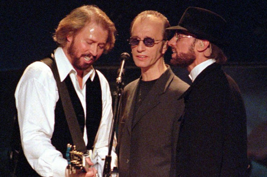 The Bee Gees, from left, Maurice, Robin and Barry Gibb sing together in their first U.S. performance in five years, at the MGM Grand in Las Vegas, Friday, Nov. 14, 1997. (Associated Press)