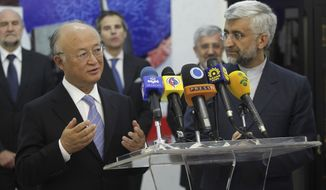 International Atomic Energy Agency (IAEA) chief Yukiya Amano (left) talks with reporters during a news briefing at the conclusion of his meeting with Iran's top nuclear negotiator, Saeed Jalili (right), in Tehran on Monday, May 21, 2012. (AP Photo/IRNA, Adel Pazzyar)