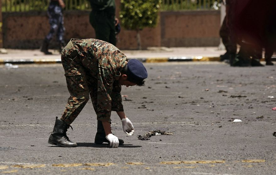 A policeman collects evidence at the site of a suicide bomb attack at a parade square in Sanaa, Yemen, on Monday, May 21, 2012. Officials said the bombing was of the deadliest attacks in the city in months. (AP Photo/Hani Mohammed)