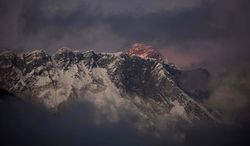 **FILE** The last light of the day sets on Mount Everest on Oct. 27, 2011, as it rises behind Mount Nuptse as seen from Tengboche, in the Himalaya's Khumbu region in Nepal. (Associated Press)