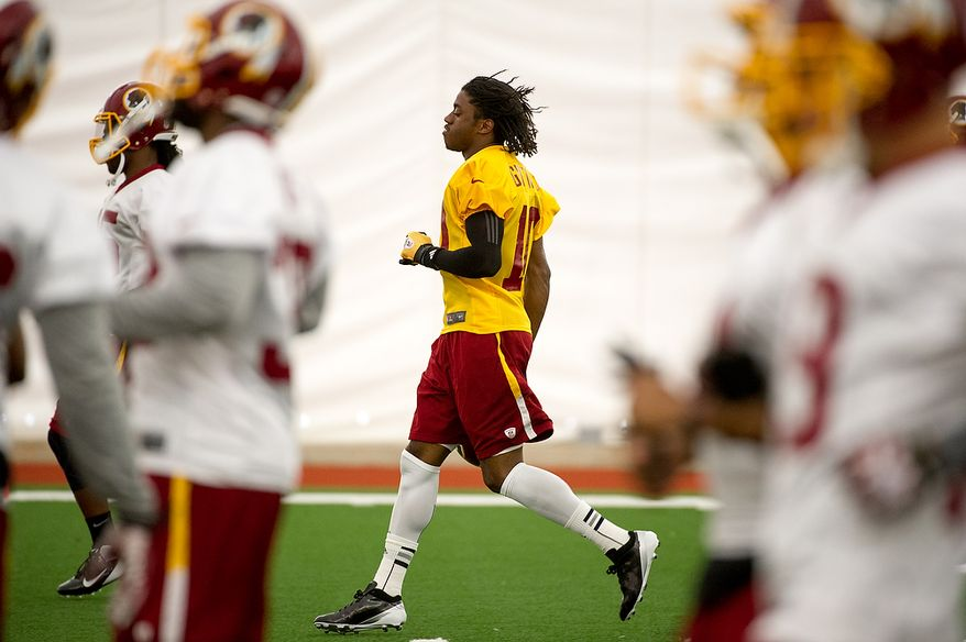 Washington Redskins quarterback Robert Griffin III warms up on the first day of organized team activity at Redskins Park, Ashburn, Va., Monday, May 21, 2012. (Andrew Harnik/The Washington Times)