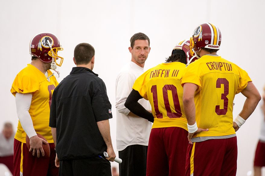 Washington Redskins offensive coordinator Kyle Shanahan, center works practice with quarterbacks Rex Grossman (8), left, Robert Griffin III (10), second from right, and Jonathan Crompton (3), throws together on the first day of organized team activity at Redskins Park, Ashburn, Va., Monday, May 21, 2012. (Andrew Harnik/The Washington Times)