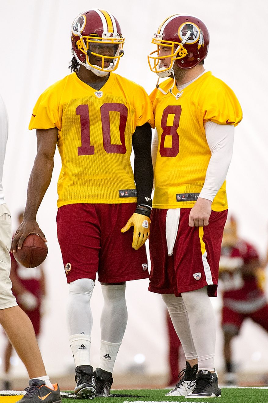 Washington Redskins quarterbacks Rex Grossman (8), right, and Robert Griffin III (10), left, talk together on the first day of organized team activity at Redskins Park, Ashburn, Va., Monday, May 21, 2012. (Andrew Harnik/The Washington Times)