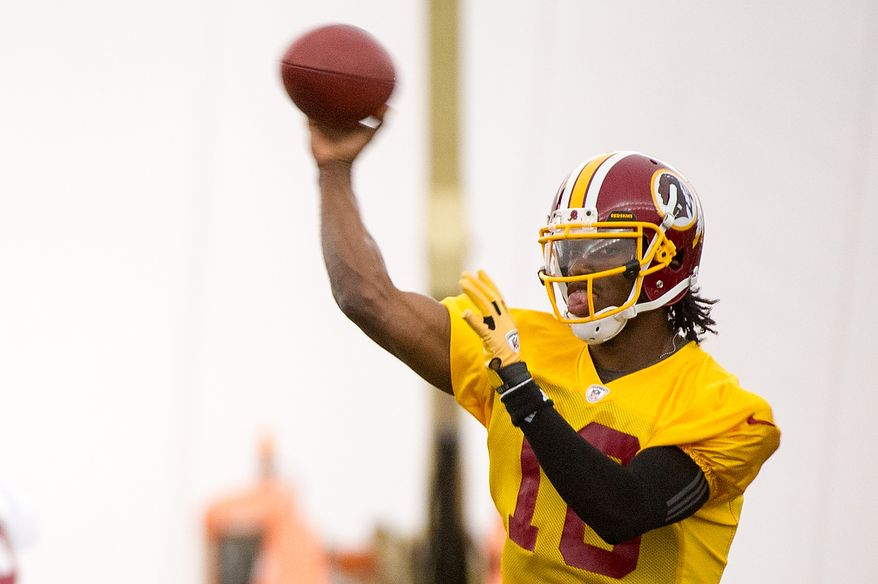 Washington Redskins quarterback Robert Griffin III (10), right, passes on the first day of organized team activity at Redskins Park, Ashburn, Va., Monday, May 21, 2012. (Andrew Harnik/The Washington Times)