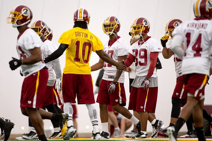 Washington Redskins quarterback Robert Griffin III (10), center left, talks with Washington Redskins wide receiver Santana Moss (89), center right, on the first day of organized team activity at Redskins Park, Ashburn, Va., Monday, May 21, 2012. (Andrew Harnik/The Washington Times)