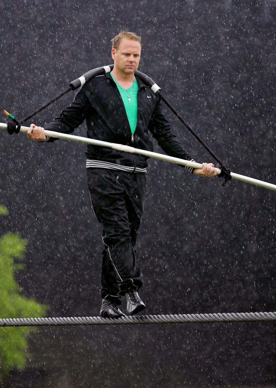 Nik Wallenda performs a walk on a tightrope in the rain during training for his walk over Niagara Falls in Niagara Falls, N.Y., earlier this month. (Associated Press)