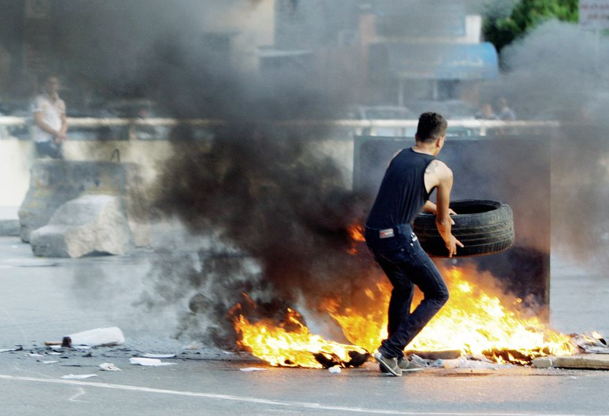 A Lebanese Shiite Muslim blocks the street in a southern suburb of Beirut on Tuesday to protest against the kidnapping of 12 Lebanese Shiite pilgrims in Syria's northern province of Aleppo by Syrian rebels. Sheik Hassan Nasrallah, the leader of Lebanon's Hezbollah militant group, has appealed for calm. (Associated Press)