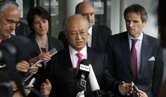 Yukiya Amano (center), director general of the International Atomic Energy Agency (IAEA), speaks to the media at Vienna International Airport near Schwechat, Austria, on Tuesday, May 22, 2012, after returning from Iran. (AP Photo/Ronald Zak)