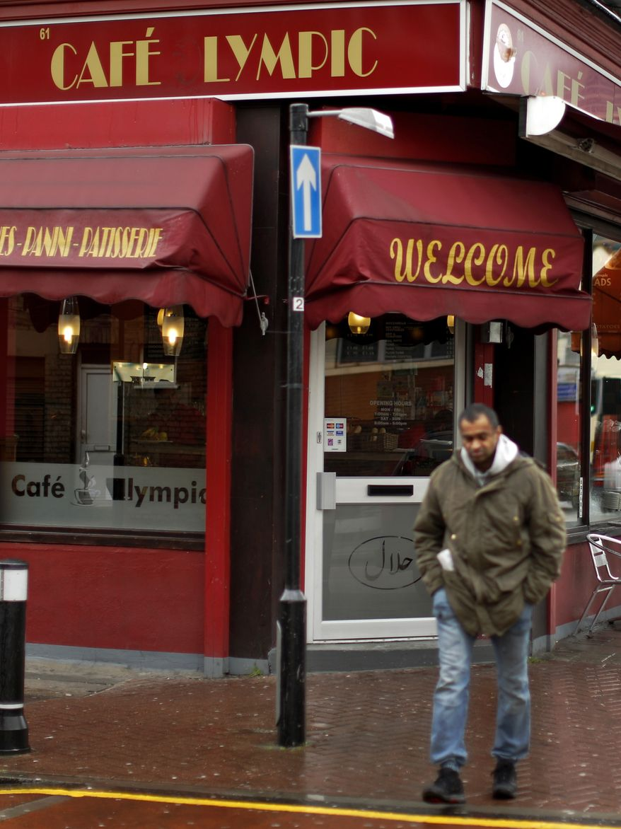 """A man walks walk past the Cafe Lympic in Stratford, east London, on  April 27, 2012. One day, the small espresso shop near the site of the London Games was the """"Olympic"""" cafe. The next day, it was the """"Lympic."""" So where did the """"O"""" go? The manager won't say. (Associated Press)"""