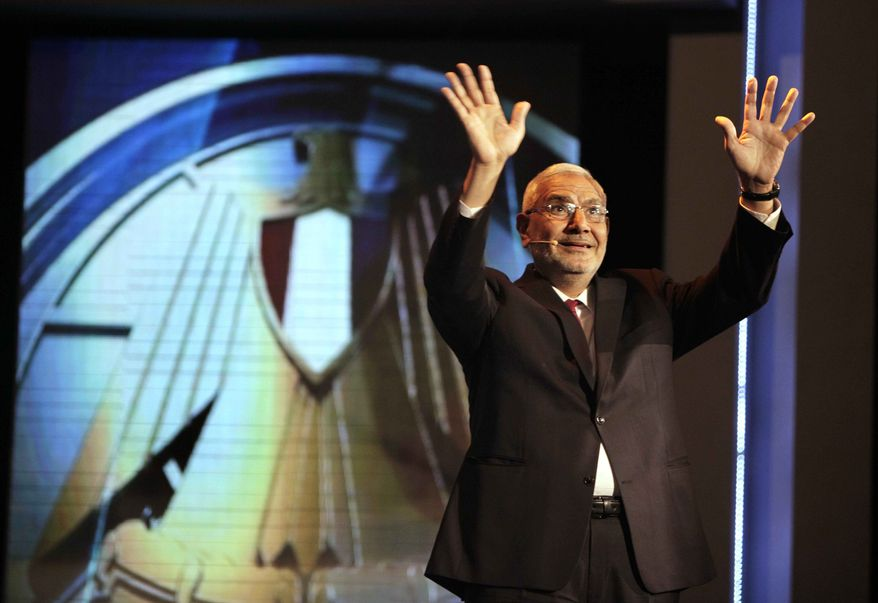 """Egyptian presidential candidate, Abdel-Moneim Abolfotoh, waves to his supporters in front of Egyptian presidency logo """" falcon"""" during television interview at MISR University for Science and Technology in Cairo, Egypt, Sunday, May 20, 2012. (AP Photo/Amr Nabil)"""