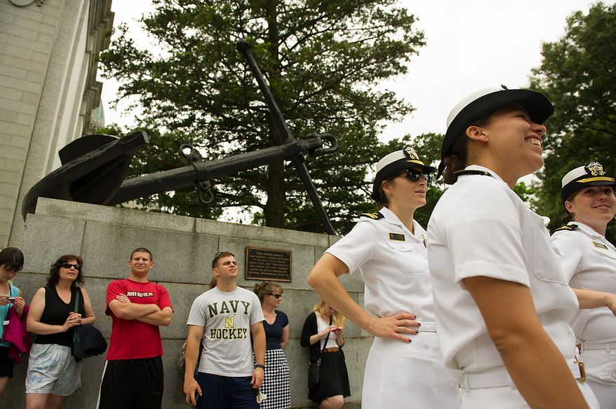 """On lookers watch as first year Naval Academy plebes participate in the traditional Herndon Monument climb which marks the culmination of their first year, Annapolis, Md., Tuesday, May 22, 2012. The tradition, dating back to 1940, involves the entire plebe class working with each other to climb the obelisk covered in lard, remove the """"dixie cup"""" hat at the top and replace it with an upperclassman's hat. (Andrew Harnik/The Washington Times)"""