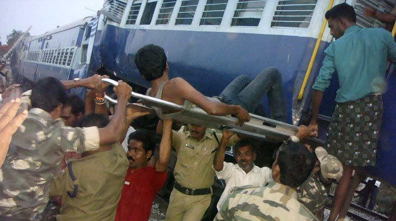 Rescuers evacuate an injured man from the site of a train accident at a station near Penukonda, India, about 105 miles north of Bangalore, on Tuesday, May 22, 2012. (AP Photo)