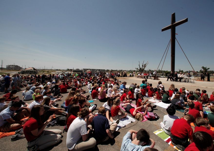 Parishioners gather around the cross at St. Mary's Catholic Church on Tuesday, May 22, 2012, in Joplin, Mo. The cross is all that remains of the church which was destroyed by a deadly tornado one year ago.  (AP Photo/Charlie Riedel)