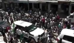 This image made from amateur video released by Shaam News Network and accessed May 22, 2012, purports to show U.N. observers being welcomed in Idlib, Syria. (Associated Press/Shaam News Network via AP video)