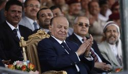 Yemeni President Abed Rabbu Mansour Hadi applauds as he watches a parade to commemorate the 22nd anniversary of Yemen's reunification, in Sanaa, Yemen, on Tuesday, May 22, 2012. (AP Photo/Hani Mohammed)