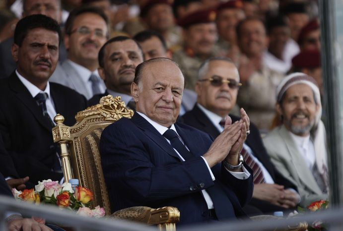 Yemeni President Abed Rabbu Mansour Hadi applauds as he watches a parade to commemorate the 22nd anniversary of Yemen's reunification, in Sanaa, Yemen, on Tuesday, May 22, 2012. (AP Photo/Ha