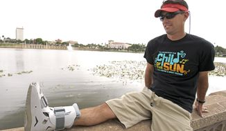 ** FILE ** In this photo taken Thursday, April 19, 2012, Greg Farris takes a break while wearing a protective boot as he helps set up for a weekend triathlon event in Lakeland, Fla. Farris injured his foot while running in barefoot running shoes.(AP Photo/John Raoux)