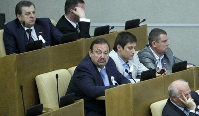 Members of the Just Russia opposition party wear white ribbons during a session of the Russian parliament in Moscow on Tuesday, May 22, 2012. Party members boycotted debates on a new bill introducing new tough sanctions against protesters. (AP Photo/Misha Japaridze)