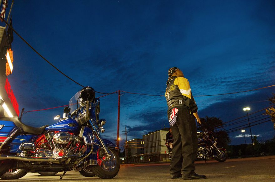 "Air Force Chief Master Sgt. Cornell ""Smokey"" Langford of Clinton stares out into the pre-dawn sky as he and other members of Rolling Thunder's Maryland chapter meet in the early-morning hours at the Harley-Davidson motorcycle shop in Fort Washington before heading to the Vietnam Veterans Memorial Wall in Washington on May 13. (Andrew Harnik/The Washington Times)"