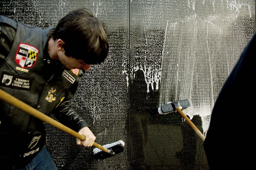 Brandon Lutzow of Waldorf, Md., helps scrub the Vietnam Veterans Memorial Wall, along with other members of Rolling Thunder's Maryland Chapter 1 on May 13 as one way of honoring the sacrifices of those who died in the war. (Andrew Harnik/The Washington Times)