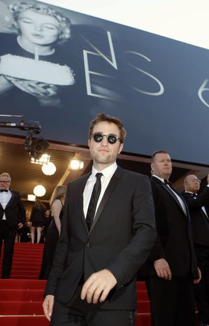 """People aren't thinking of me as a kid anymore, so I've got to stop behaving like one,"" said Robert Pattinson, shown arriving for the screening of ""On the Road"" on Wednesday at the Cannes Film Festival. (Associated Press)"