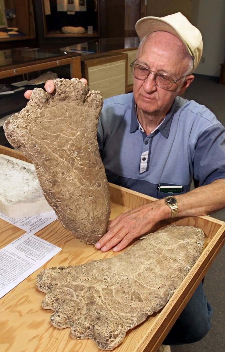 """**FILE** Al Hodgson, a volunteer guide at the Willow Creek-China Flat Musuem, holds up a plaster cast of a Bigfoot imprint displayed at the museum's new """"Bigfoot Wing"""" in Willow Creek, Calif., on June 5, 2000. (Associated Press)"""