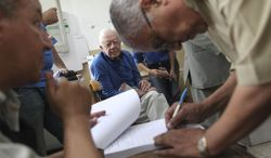 Former U.S. President Jimmy Carter, center, observes the election process inside a polling station in the Sayeda Aisha neighborhood of Cairo, Egypt, Wednesday, May 23, 2012. (AP Photo/Thomas Hartwell)