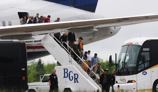 Passengers deplane from a diverted trans-Atlantic US Airways flight on the tarmac at Bangor International Airport in Bangor, Maine, on Tuesday, May 22, 2012, after a French passenger passed a note to a flight attendant saying she had a surgically implanted device. (AP Photo/Bangor Daily News, Kevin Bennett)